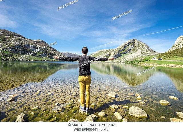 Spain, Asturias, Picos de Europa National Park, man standing with raised arms at Lakes of Covadonga