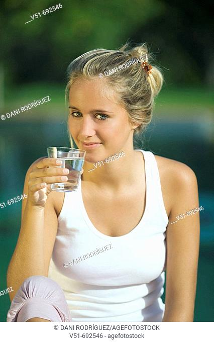 Portrait of a young woman holding a glass of water