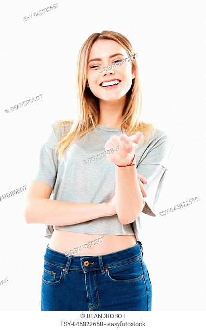 Portrait of a happy smiling girl pointing finger at camera isolated over white background