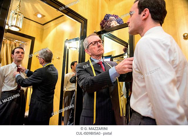 Tailor fastening customer's tie in tailors shop