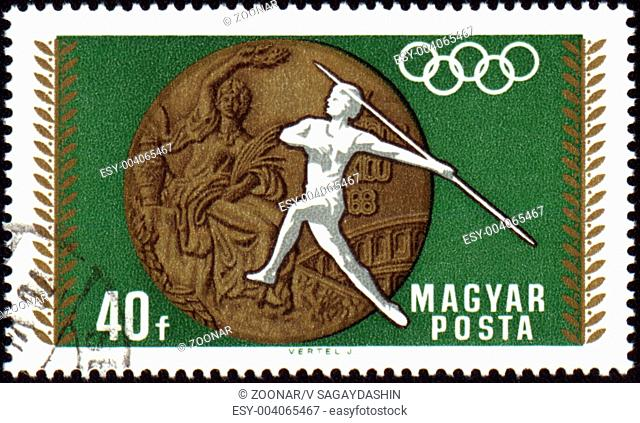 HUNGARY - CIRCA 1968: A post stamp printed in Hungary shows javelin throwin and Olympic medal