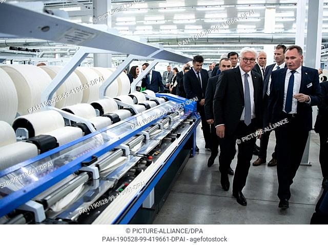 28 May 2019, Uzbekistan, Taschkent: Federal President Frank-Walter Steinmeier (l) visits the Bakan Tex yarn spinning mill and is guided through the production...