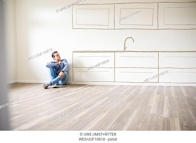 Young man in new home sitting on floor thinking about interior design
