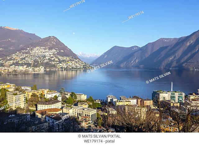 View over City and Alpine Lake Lugano with Mountain and the Moon in Switzerland