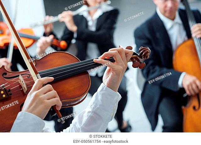 Classical music symphony orchestra string section performing, female violinist playing on foreground, hands close up