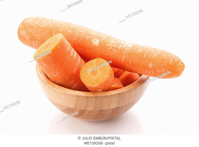 whole carrots and cut in wooden bowl isolated on white