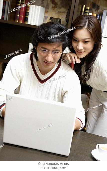 Young couple playing with laptop