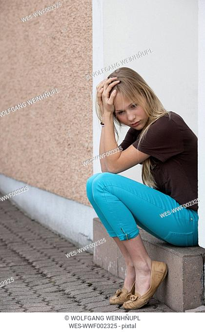 Austria, Teenage girl with head in hand sitting at doorstep