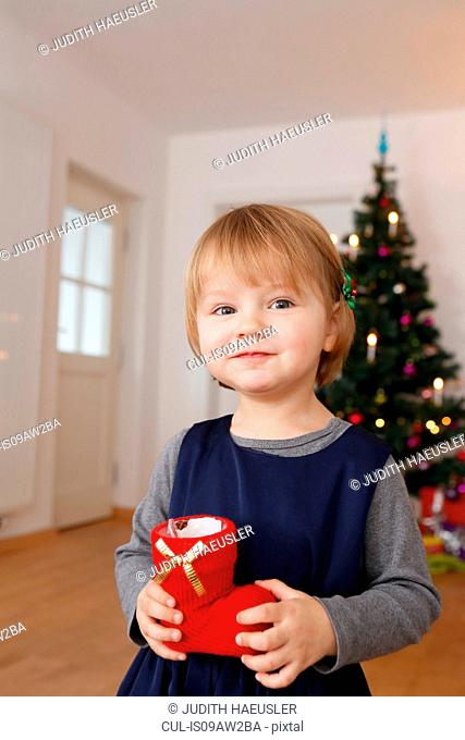 Girl in front of christmas tree holding red boot looking at camera smiling