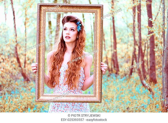 Ravishing beautiful redhead long haired woman wearing a low-cut sleeveless dress with floral pattern while looking at camera through a brown handheld portrait...