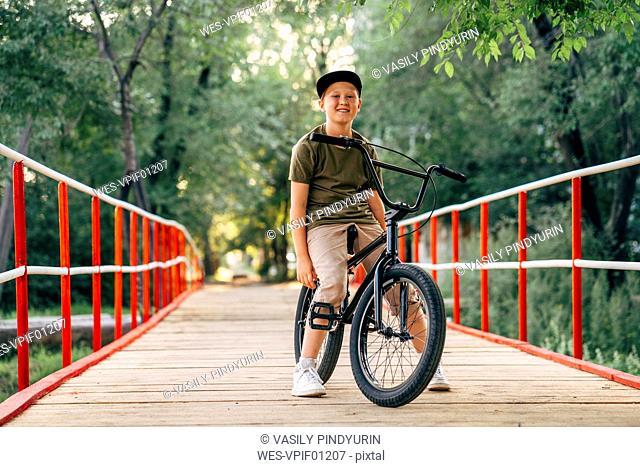 Portrait of smiling boy with bmx bike on bridge