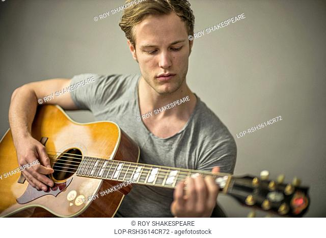 England, London, Hackney. A beautiful young man playing acoustic guitar