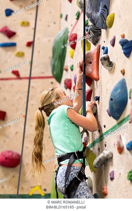 Caucasian girl climbing rock wall indoors