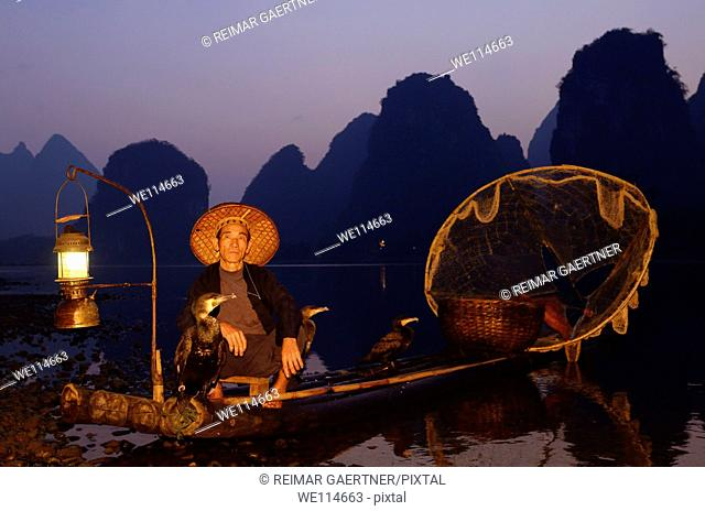 Fisherman with cormorants on bamboo raft at dawn on the shore of the Li river Yangshuo China