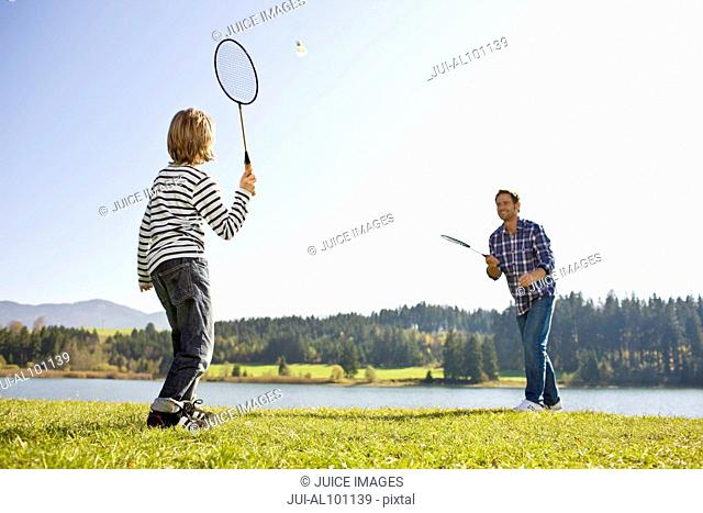 Father and son playing badminton near lake