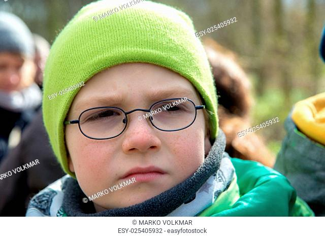 boy with green cap is looking serious
