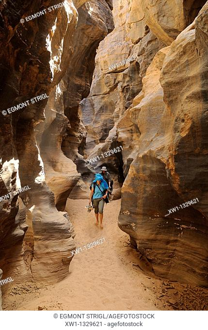woman hiking through a gorge at El Ghessour, Tassili du Hoggar, Wilaya Tamanrasset, Algeria, Sahara, North Africa