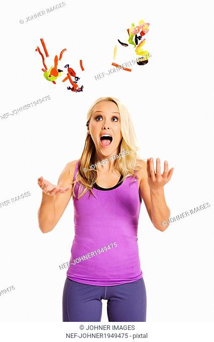 Young woman throw sweets, studio shot