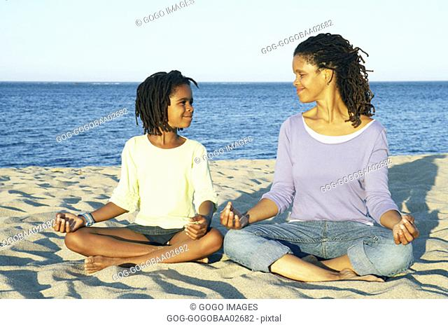 Young African woman meditating with her son on the beach