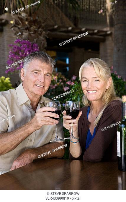 Mature couple having red wine