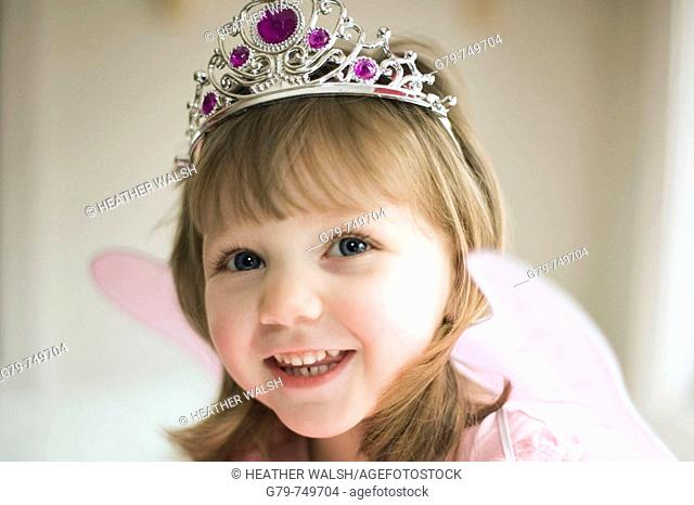 Young girl smiling wearing butterfly wings and tiara