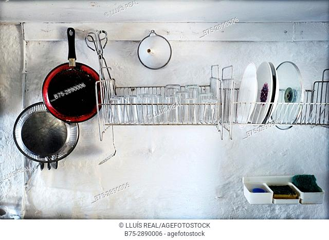 Old and simple kitchen in a fishing lodge with cooking utensils, pots, dishes, etc. Sa Mesquida, Mahó, Minorca, Balearic Islands, Spain