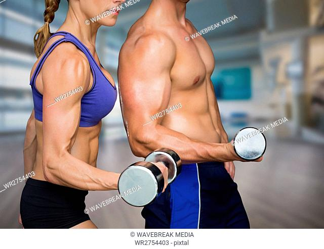 Man and Woman mid sections weightlifting in blurry gym