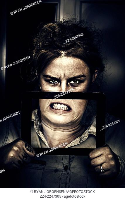 Funny technology portrait of a caucasian woman snarling on the screen of a tablet computer screen. Gadget mad