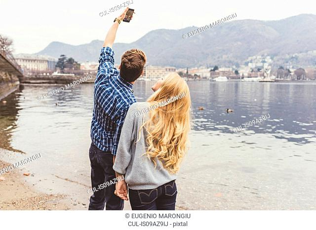 Young couple taking smartphone selfie on lakeside, Lake Como, Italy