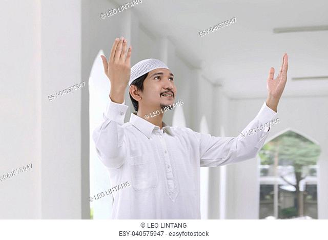 Smiling asian muslim man with traditional dress pray to god in the mosque