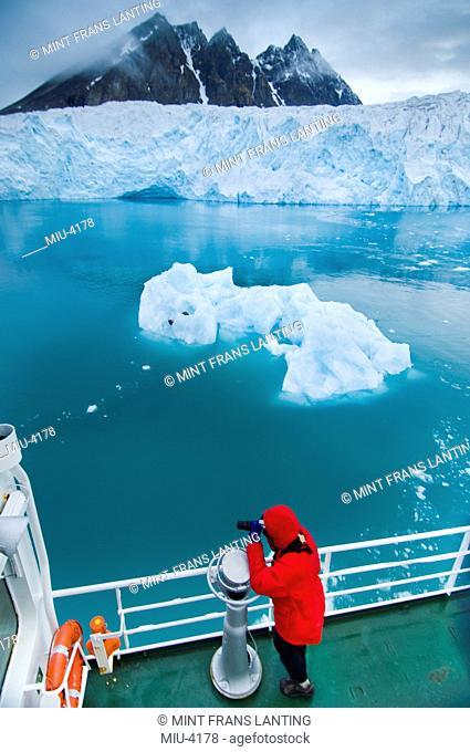 Tourist photographing iceberg, Monaco glacier, Svalbard, Norway