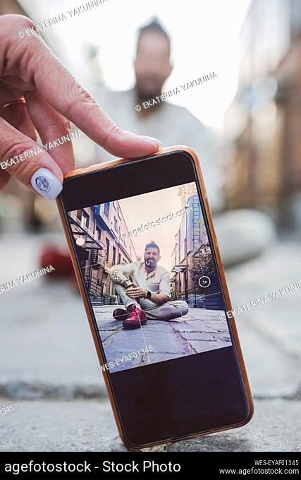 Woman photographing man through smart phone on footpath in city