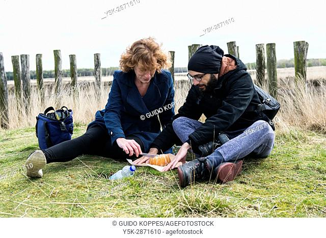 Regte Heide, Netherlands. Young man and woman celebrating easter with a cake, while sitting down on top of a pre-historic barrow