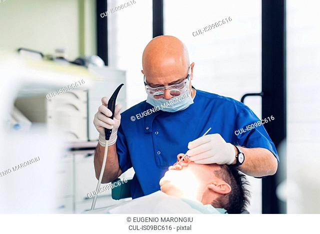 Dentist carrying out dental procedure on male patient