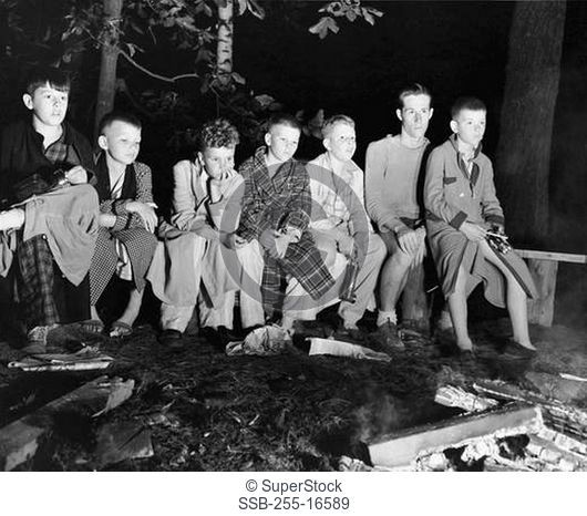 Group of boys sitting side by side in front of a campfire