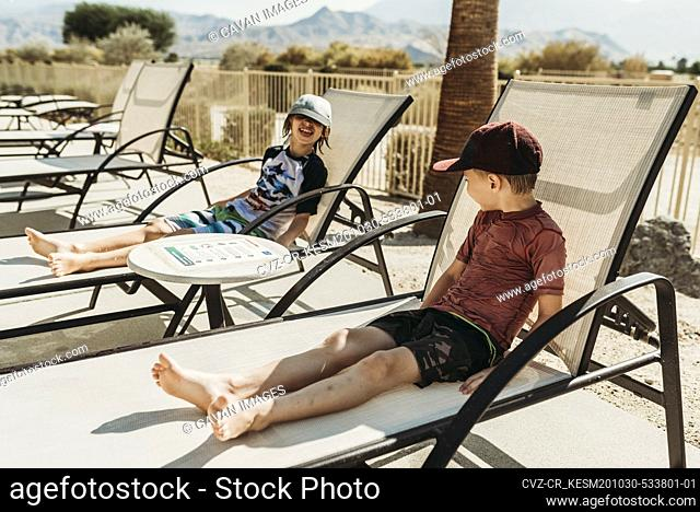 Close up view of young brothers in pool chairs laughing together