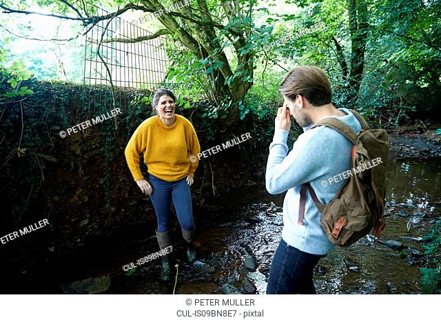 Hiker couple taking photograph in stream