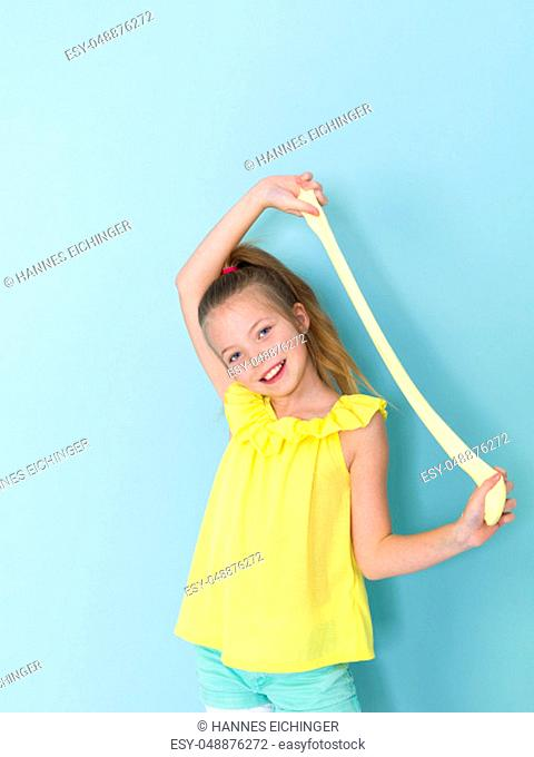 beautiful 9 year old girl is playing with yellow slime in front of blue background