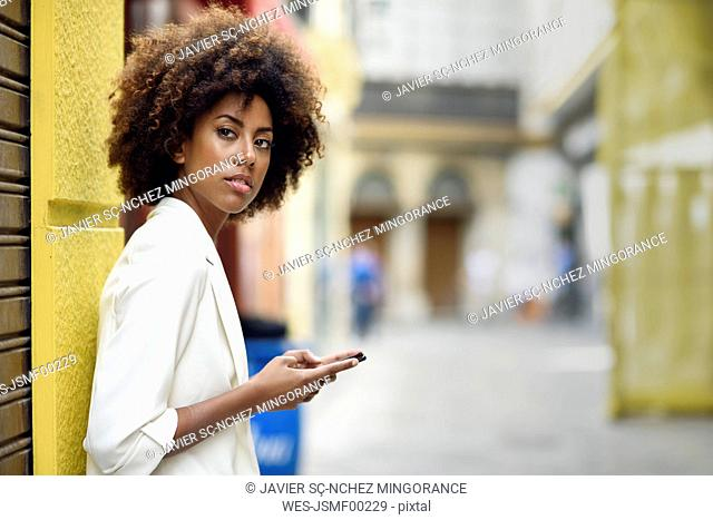 Portrait of waiting young woman with cell phone