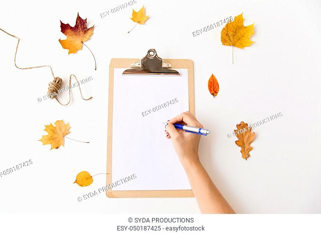 hand writing on white paper on clipboard in autumn