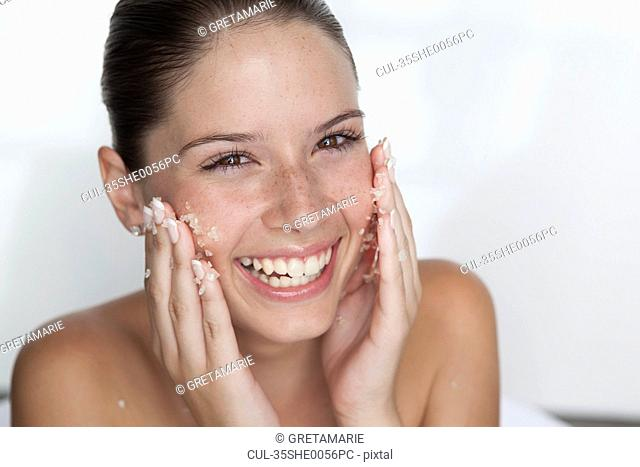 Woman scrubbing sugar on her face