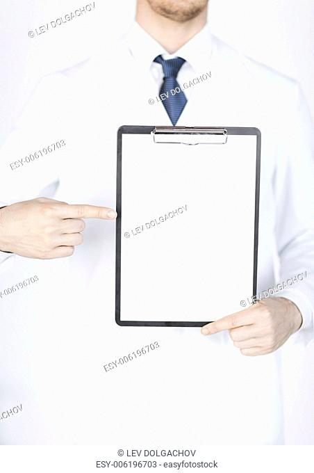 close up of doctor pointing at blank white paper