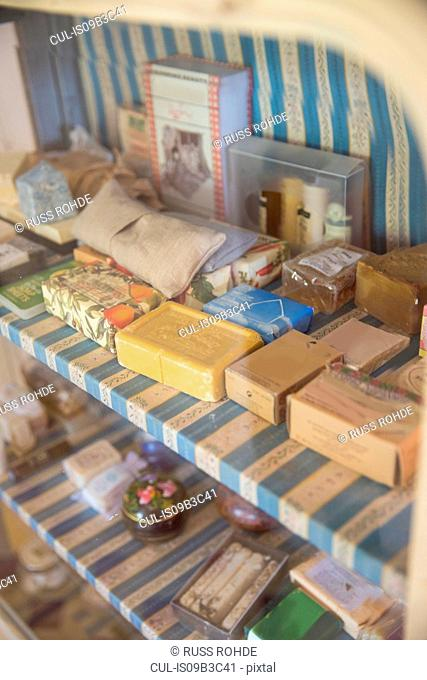 Vintage soap bars on display cupboard in handmade soap workshop