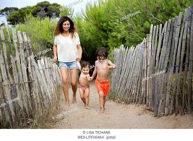 Happy mother and two children walking hand in hand on beach path