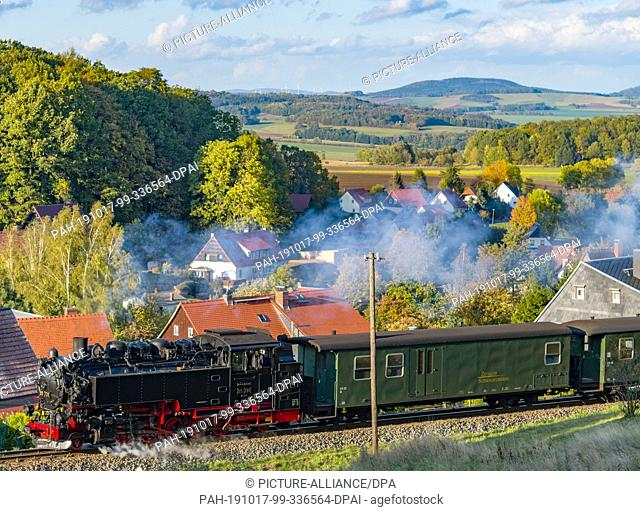 10 October 2019, Saxony, Jonsdorf: A steam locomotive of the Zittau narrow-gauge railway runs through the autumn landscape