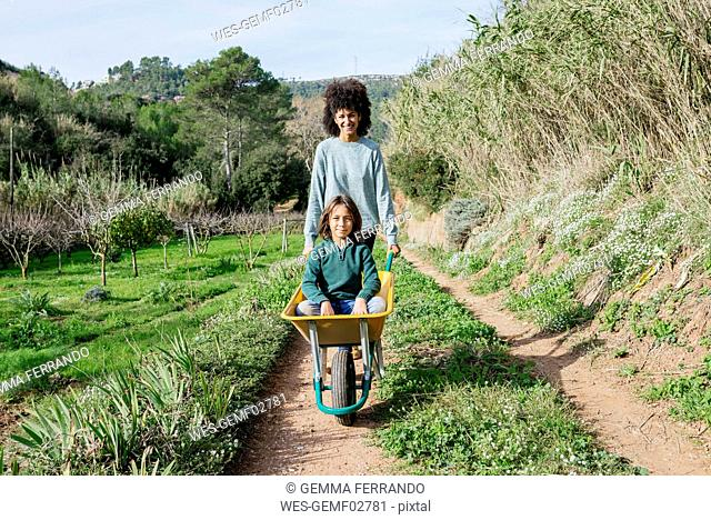Mother walking on a dirt track, pushing wheelbarrow, with his son sitting in it
