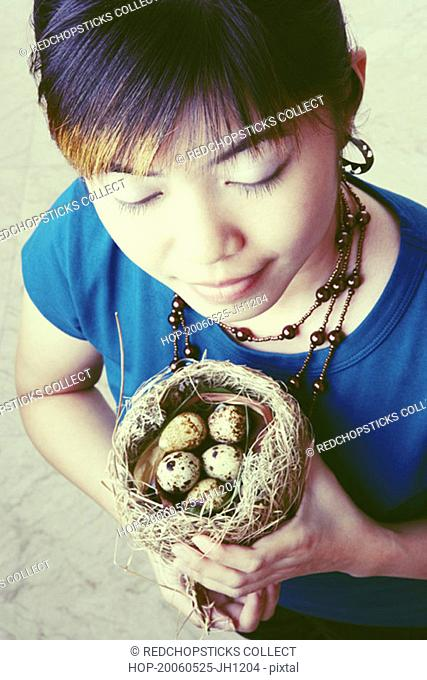 High angle view of a young woman holding a nest with eggs