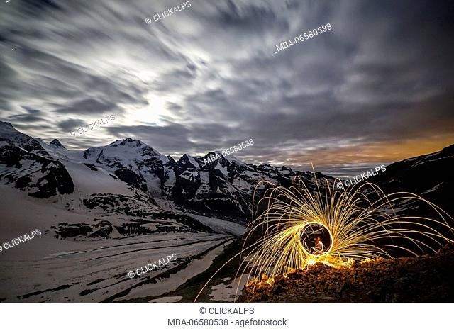 Steel wool at Diavolezza refuge with full moon and Pizzo Bernina with its glaciers, Pontresina, Engadine, Canton of Graubunden, Switzerland Europe