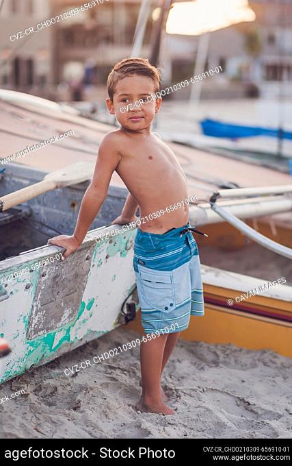 Young boy sitting on a docked boat at the beach
