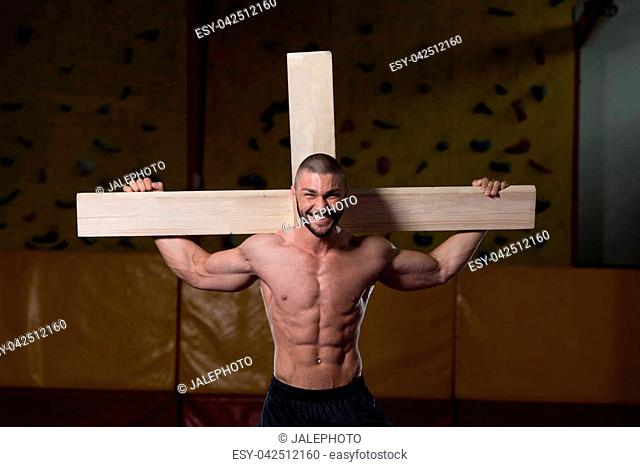 Portrait Of A Young Physically Fit Man Dragging a Wooden Cross In A Gym - Muscular Athletic Bodybuilder Fitness Model Posing After Exercises
